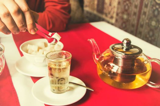 man puts sugar in tea, restaurant,East style