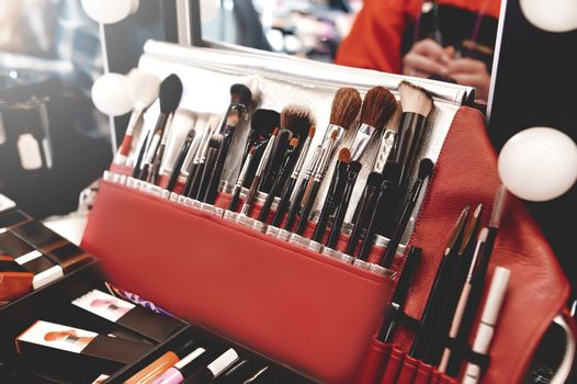 Closeup of makeup tools. Professional makeup brushes in tube, leather bag on a wooden table. Set of different objects for makeup artist in their holder.