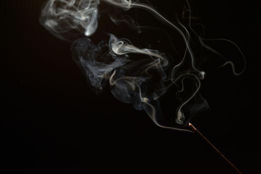 smoldering aromatic stick in the dark, a lot of smoke