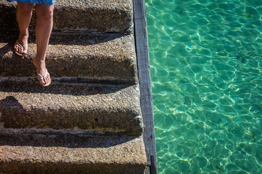 Legs of a woman going downstairs on a concrete stairs leading down to the sea of torquoise water