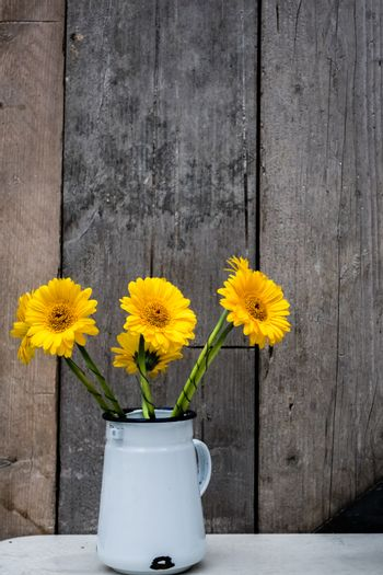 Yellow gerbera flowers in a metal pot on a table outside restaurant