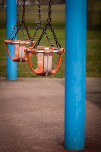 Two empty swings in an outdoor playground