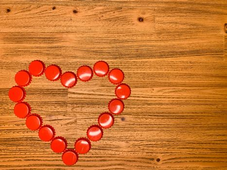 Red love heart made from beer bottle tops lids on a rustic wooden table. Beer drinkers Valentine's day concept, top view horizontal stock image with empty space for text