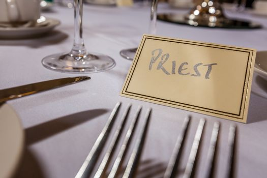 Priest seat at a table at wedding reception