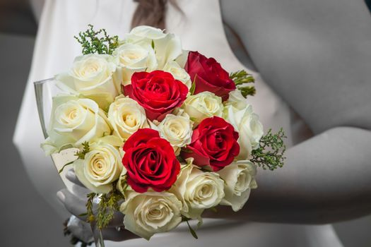 Bride holding a wedding bouquet of red and white roses