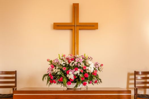Christian cross, altar, candle and flower bouquet in a church chapel.