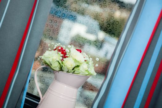 Watering can containing red and white roses wedding bouquet