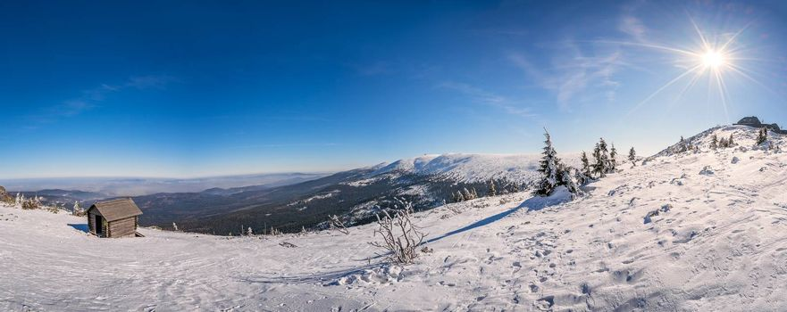 Panoramic view of a Karkonosze mountains with a small wooden hut on the slope of Szrenica mountain in the foreground, Poland