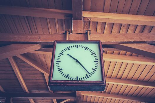Old retro clock at the train station with a wooden roof in the background
