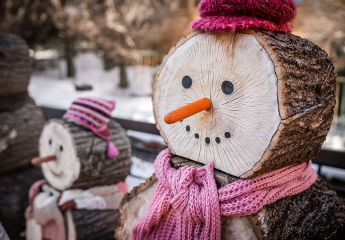 Close up of a nose of a snowman made of wooden log wearing purple and pink hat and scarf