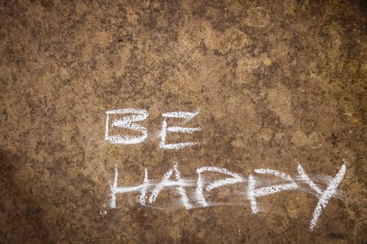 Words saying be happy written in chalk on a rough grungy wall backdrop