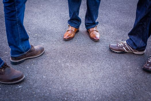 Close up of legs and feet of three friends standing on a street and talking
