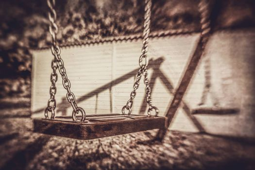 Retro sepia picture of an swing in an outdoor playground