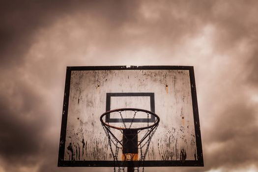 Old disused outdoor basketball hoop on a stormy, cloudy day