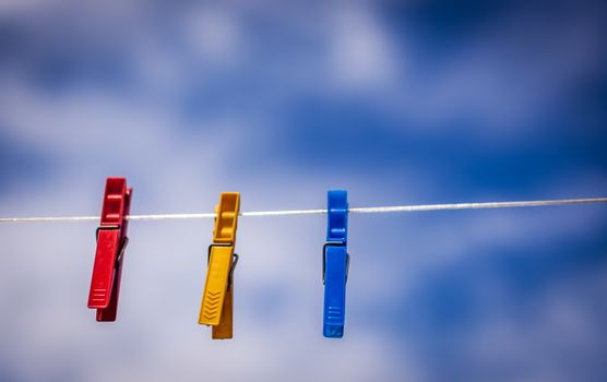 Three colorful laundry clips hanging on a cloths line