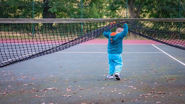 Little boy walking under the net on the tennis court