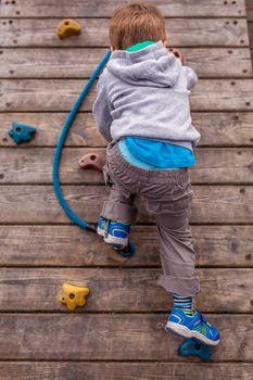Sporty little boy climbing artificial boulder wall on an outdoor playground