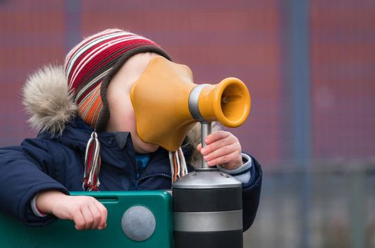Little Caucasian boy shouting inside a playground megaphone