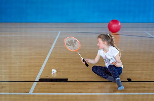 Cute little Caucasian girl playing badminton in an indoor sport and leisure centre