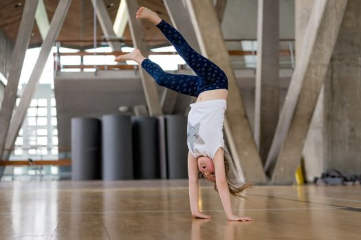 Young Caucasian girl doing cartwheel on the floor in an indoor sports centre