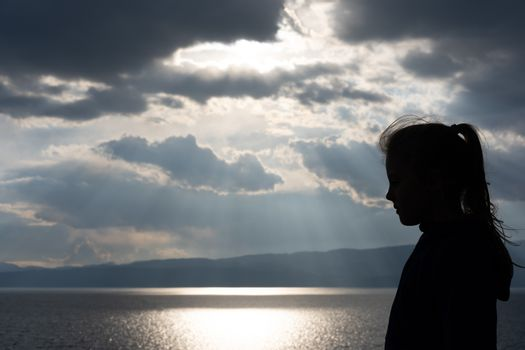 Silhouette of a little young girl with a ponytail on the shore of Lake Ohrid, Republic of Macedonia