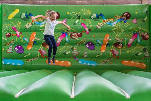 Cute young seven years old Caucasian girl jumping inside the inflatable bouncy castle