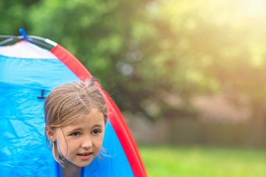 A young girl peering through an opening in a tent on a camping ground in summer
