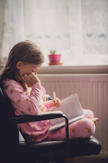 Cute little Caucasian girl sitting by the window in her pyjama in the morning reading a childrens book