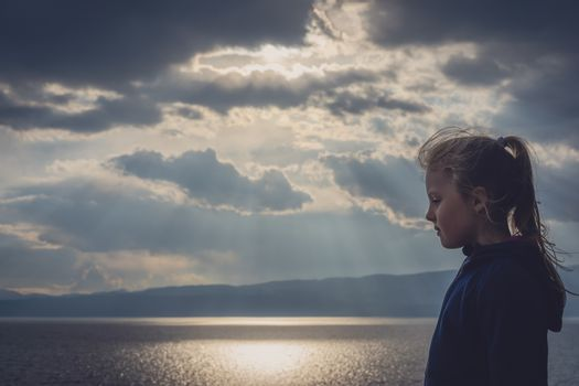 Little young girl with a ponytail on the shore of Lake Ohrid, Republic of Macedonia