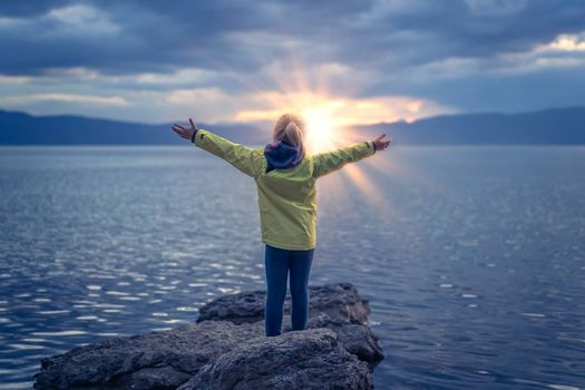 Triumphant little girl lifting her hands high in the air while standing on the large boulders on the shore of Lake Ohrid, Republic of Macedonia