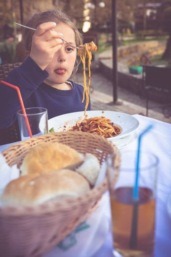 Portrait of a cute little girl eating spaghetti pasta for dinner in an outdoor table restaurant