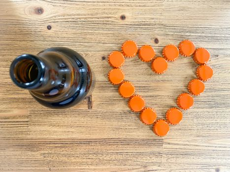 An orange love heart made from beer bottle tops lids and a brown glass beer bottle on a rustic wooden table. Beer drinkers and lovers Valentine's day concept top view horizontal image