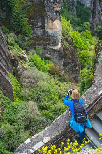 Female tourist standing on a stairs leading to the Great Meteoron Monastery and taking pictures of the landscape at Meteora, Trikala region, Greece