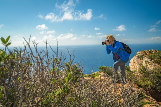 Female tourist standing on the edge of a cliff and photographing the stunning cliffs in Shipwreck Cove in summer on Zante Island, Greece