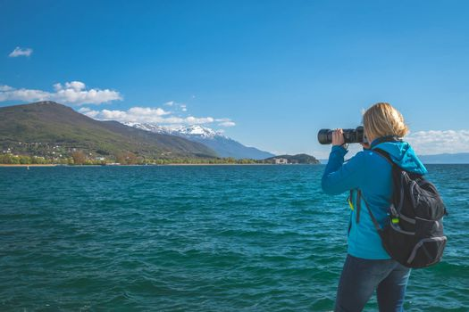 Blond Caucasian female backpacker taking pictures of the stunningly beautiful Ohrid Lake, Northern Macedonia