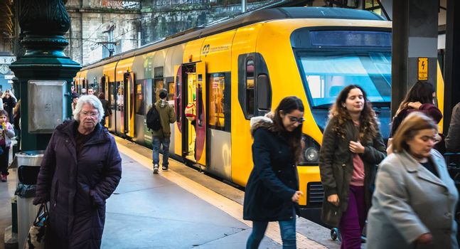 Porto, Portugal - November 30, 2018: Interior of Porto Sao Bento train station where people walk on the dock near the train stationary on a winter day