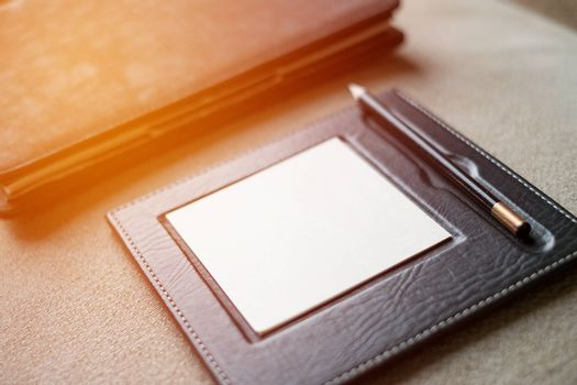 Black leather note book with pencil on carpet background