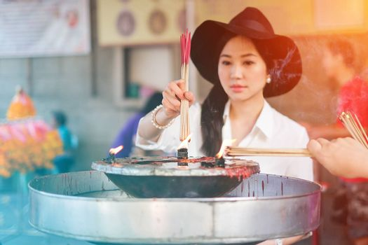 Woman holding burning incense sticks in chinese temple