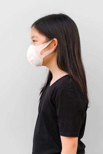 Side view of Asian kid wearing mask protecting herself from COVID-19 or Corona Virus.