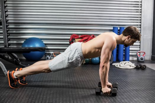 Man doing push up with dumbells