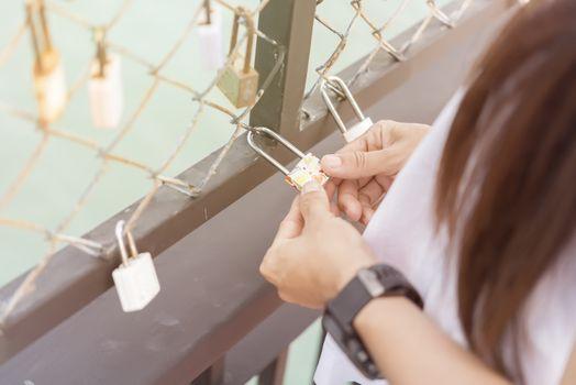 Women hand holding master key  with bridge rail locks of love so