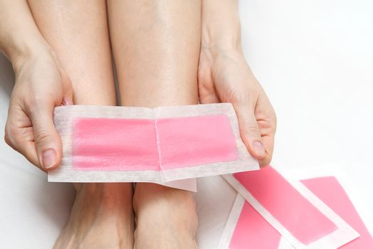 Woman using pink wax strips. Beautiful woman doing depilation for her legs with waxing, isolated on white