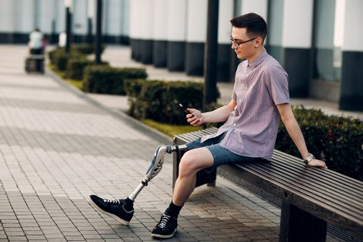Disabled young man with foot prosthesis sitting and hold mobile phone outdoor