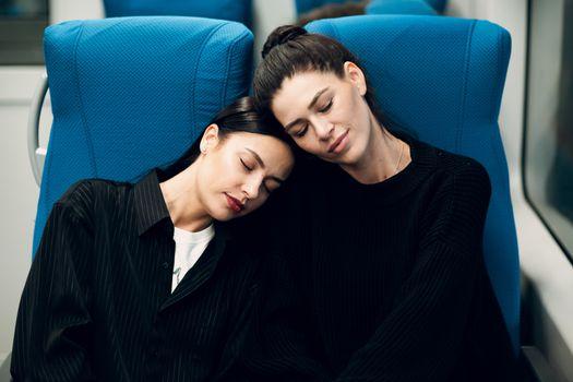 Two young women sleeping in  train