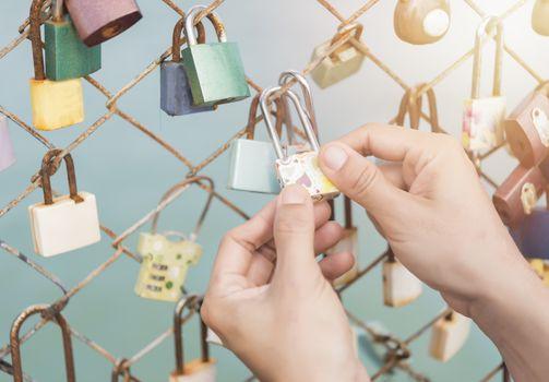Women hand holding master key  with bridge rail locks of love