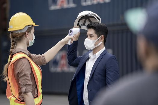 Factory woman worker in a face medical mask and safety dress used measures temperature at worker people standing on queue with a non-contact infrared thermometer. background of cargo container.