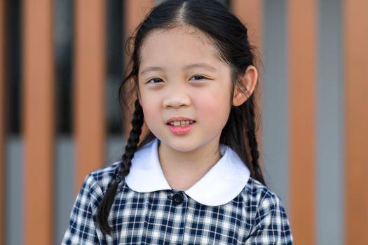 Smiling kid, girl, in school uniform portrait.