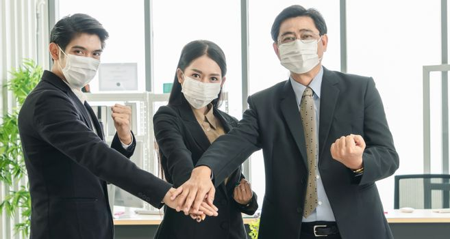 Stop Covid-19-Concept. A team of Asian businessmen wear masks to protect and prepare to fight the pandemic virus worldwide.