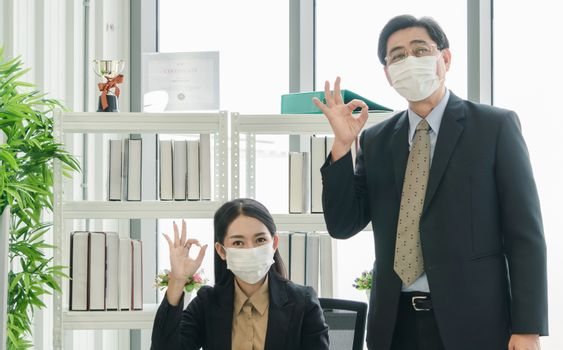 A team of Asian businessmen wear masks to protect and prepare to fight the pandemic virus worldwide. A team of Asian businessmen wearing black suits are working together in the office.