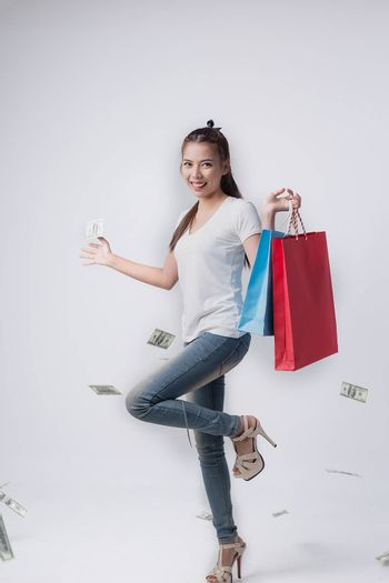 Pictures of beautiful cheerful girls in summer dress, holding dollar bills with shopping bags and looking at camera through white background.